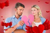 Couple holding two halves of broken heart against red vignette
