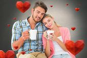 Attractive young couple sitting holding mugs against white background with vignette