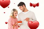 Attractive couple holding miniature house model against hearts