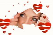 Woman looking through torn paper against hearts
