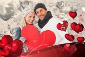 Smiling couple in winter fashion posing with heart shape against grey valentines heart pattern