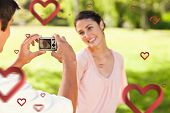 Man takes a photo of his smilng friend against hearts
