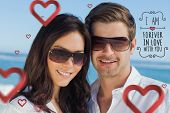 Smiling couple wearing sunglasses and looking at camera against valentines message