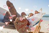Close up of sandy feet of couple in a hammock against happy valentines day