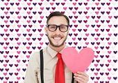 Geeky hipster smiling and holding heart card against valentines day pattern
