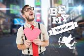 Geeky hipster crying and holding heart card against blurred new york street