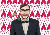 Geeky hipster holding rose between teeth against valentines day pattern