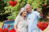 Cheerful mature couple taking pictures of themselves against valentines love hearts
