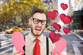 Geeky hipster crying and holding broken heart card against blurry new york street