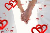 Bride and groom holding hands close up against hearts
