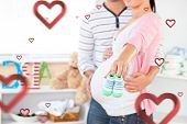 Close up of a bright pregnant woman holding baby shoes while husband touching her belly in the room against hearts