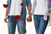 Hip young couple holding hands against red love hearts