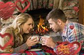 Couple with tea cups in front of lit fireplace against happy valentines day