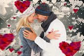 Happy couple in winter fashion embracing against grey valentines heart pattern