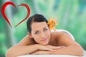Beautiful brunette relaxing on massage table smiling at camera against heart