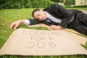 stock photo of unemployed people  - Frustrated unemployed man with sign lying down the lawn - JPG