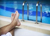 stock photo of pov  - Sunbathing by the hotel tourist resort swimming pool mans legs lying down on a sunlounger - JPG
