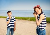 stock photo of tin can phone  - Kids having a phone call with tin cans on sea background - JPG