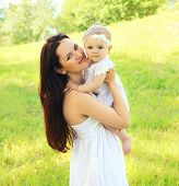 image of mother baby nature  - Sunny portrait of beautiful young mother and baby together on the nature - JPG