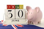 foto of piggy  - End of Financial Year Savings Concept with piggy bank building blocks and wood calendar and Australian Flag on white wood table - JPG