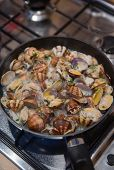 stock photo of clam  - Cooking some clams with wine and parsley in the pan - JPG