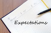 stock photo of expectations  - Yellow blank notepad on office wooden table Expectations concept - JPG