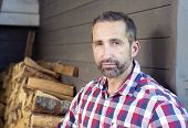 picture of firewood  - portrait of a man in a plaid shirt in front of firewood - JPG