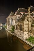 stock photo of gents  - The historical buildings of Gent in Belgium at night with reflections in the river Scheldt - JPG