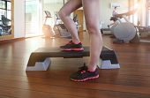stock photo of step aerobics  - Step aerobics. Cropped image of beautiful young woman doing step aerobics while in health club