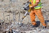 foto of reinforcing  - Construction worker holding jackhammer and breaking reinforced piles in the ground - JPG