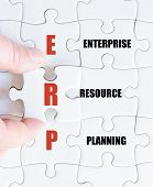 foto of enterprise  - Hand of a business man completing the puzzle with the last missing piece - JPG