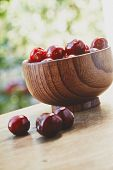 picture of berries  - Vertical photo of cherry berries in the wooden bowl on the wooden table on the green bokeh background with three berries out of the bowl - JPG