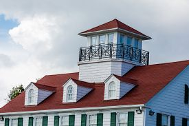 picture of gabled dormer window  - Cliassic white home with red roof dormers and widows walk - JPG