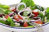 Greek salad in old enamel bowl, on wooden table.