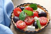 Small tart with cherry tomatoes, goat's cheese, black olives and spinach.