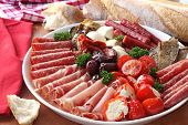 Platter of antipasto, with crusty bread.  A mixture of salami, prosciutto, bocconcini, grilled peppe