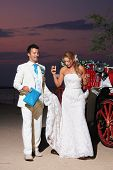 Beach wedding: bride and groom and carriage by the sea