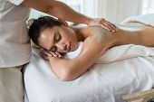 Young Beautiful Asian Woman Relaxing In The Spa Massage And Having Salt Scrub Massage At Back. Healt poster