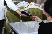 Credit Card Terminal For Cashless Payments. Cashiers Hand Holds Credit Card Reader On Restaurant Bac poster