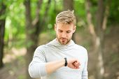 Sportsman Training With Pedometer Gadget. Man Athlete On Busy Face Check Fitness Tracker, Nature Bac poster
