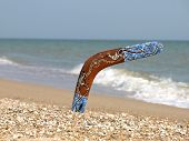image of boomerang  - Boomerang on Sandy Beach Against of Sea Surf - JPG