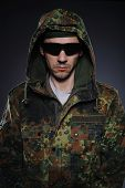 Portrait Of Soldier In Camouflage And Ammunition . Studio Shot
