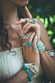 closeup of young woman hands lot of boho style jewelry, rings and bracelets outdoor summer day poster