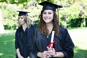 Pretty young woman at graduation holding diploma
