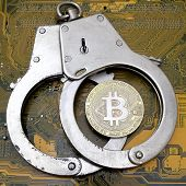 The Real Bitcoin Coin Lies On Closed Steel Handcuffs Against The Yellow Computer Electronics Board.  poster
