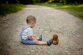 Little Boy Playing With Teddy Bear On The Footpath. poster