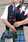 stock photo of bagpiper  - Playing the Scottish bagpipes on the streets of Fort William