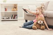 Bored Little Girl Watching Tv At Home. Female Kid Sitting On Floor Carpet With Her Toy Friend Teddy  poster