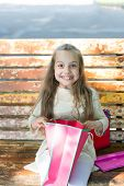 Girl On Happy Face Unpacking Shopping Bags Or Presents, Bench On Background. Girl Surprised By Unexp poster