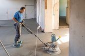 Laborer Performing And Polishing Sand And Cement Screed Floor. Sand And Cement Floor Screed. poster